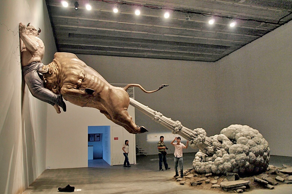 "In this photo taken Sunday, Sept. 27, 2009, a sculpture by Chinese artist Chen Wenling entitled ""What You See Might Not Be Real"" is on display at a gallery in Beijing, China. The artwork is a critique of the global financial crisis with the bull representing the golden bull of wall street and the man pinned to the wall representing the jailed financier Bernard Madoff. (AP Photo/Ng Han Guan)"