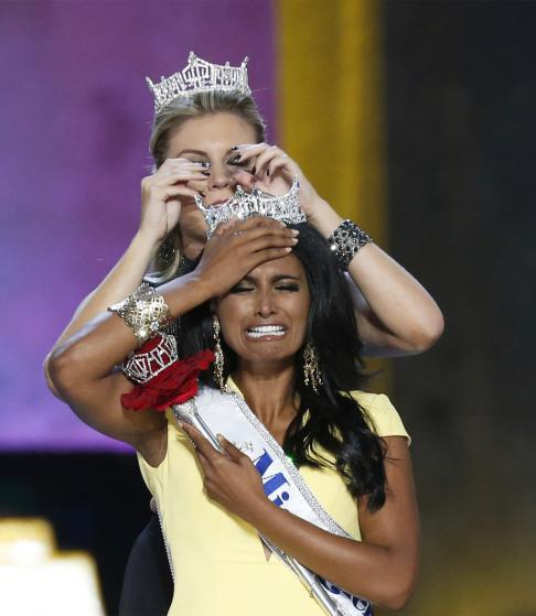 Miss America contestant, Miss New York Nina Davuluri reacts after being chosen winner of the 2014 Miss America Pageant as 2013 Miss America Mallory Hagan places a tiara on her head in Atlantic City, New Jersey, September 15, 2013. Davuluri, 24, won the 2014 Miss America Pageant on Sunday, giving the prize to Miss New York for the second year in a row. REUTERS/Lucas Jackson (UNITED STATES - Tags: ENTERTAINMENT SOCIETY TPX IMAGES OF THE DAY) - RTX13MWM